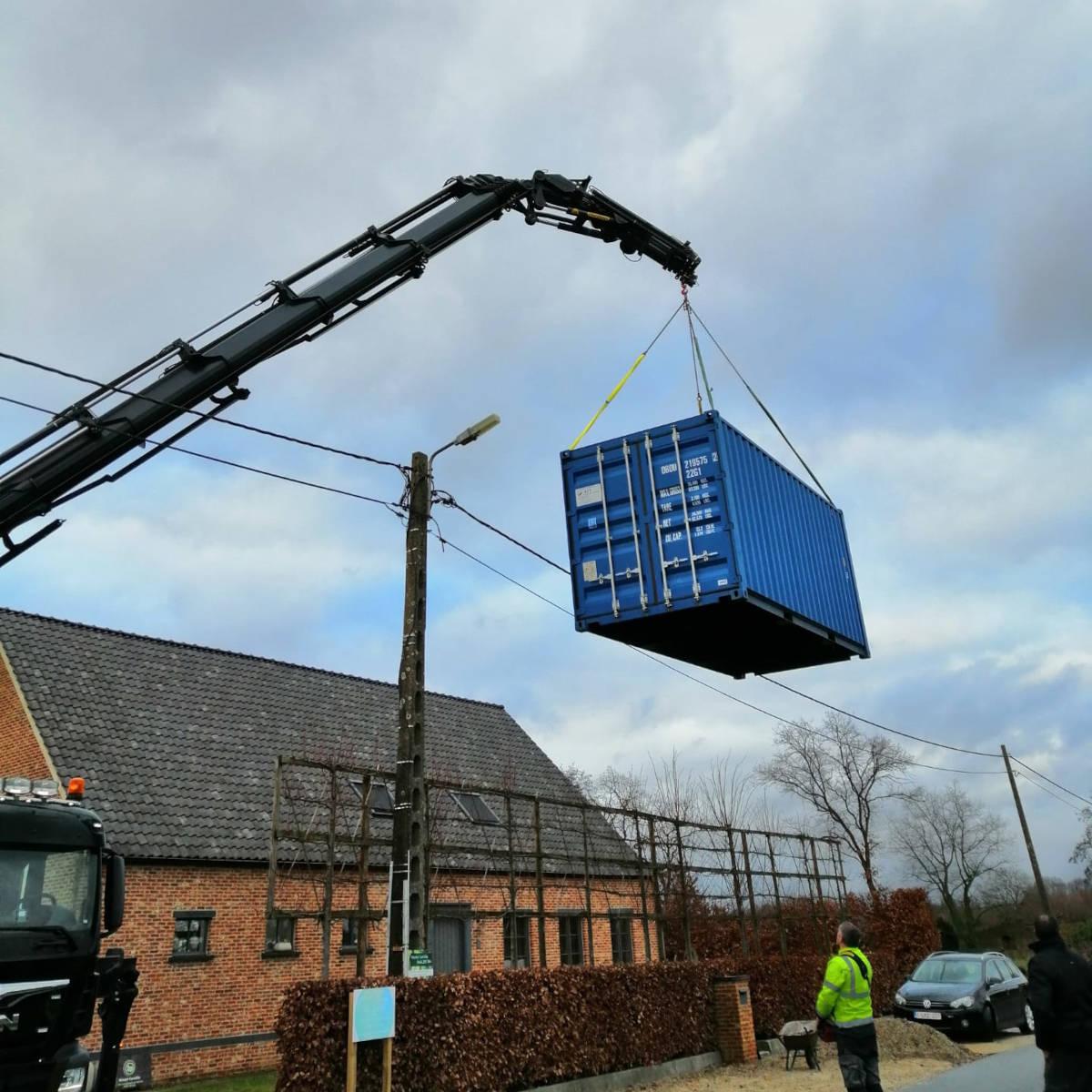 de kraanwagen die een container over een huis tilt.